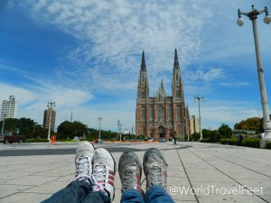 Dos pares de pies viajeros recorriendo La Plata y de fondo la Catedral de la Inmaculada Concepción.