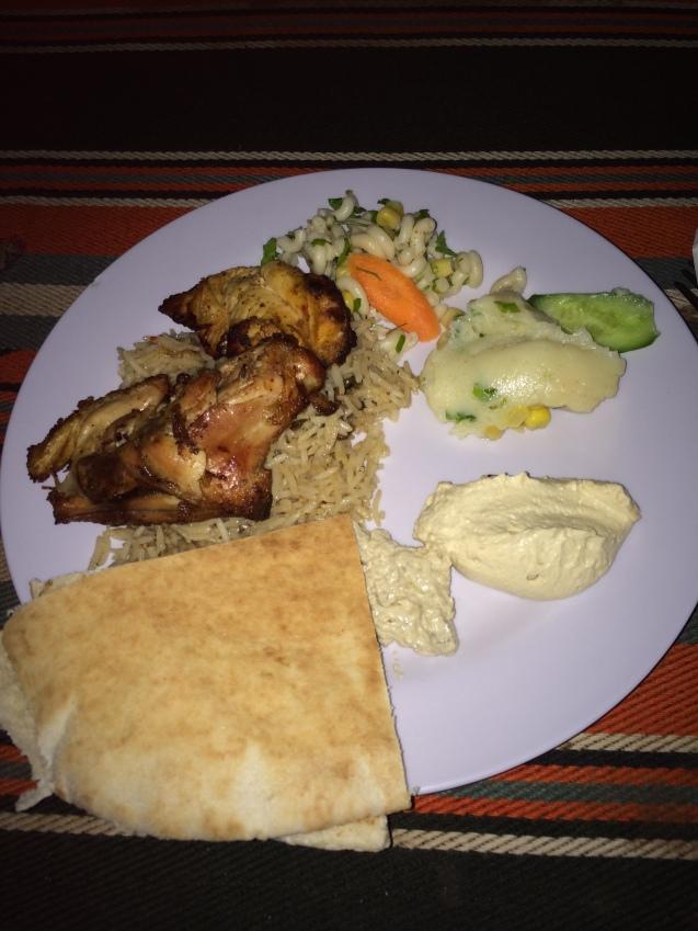 Pollo cocinado bajo tierra, con arroz, humus y pan árabe. ¡Delicia total!